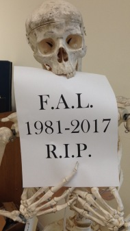 "Skeleton with a sign reading ""F.A.L. / 1981-2017 / R.I.P."""